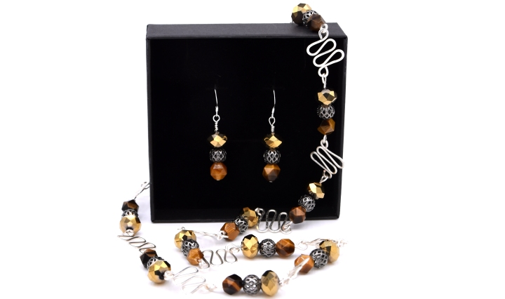 Gabriella Szekely jewellery - filigree and glass bead pendant and earing as a set displayed in a jewellery box - silver beads golden glass bead and tiger eye brown orange beads with handmade findings